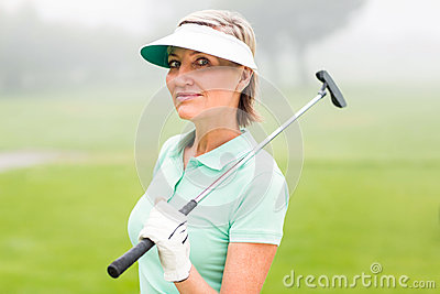 Golfer standing and swinging her club smiling at camera