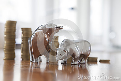 Stock market, bull and bear, figurines, stack of coins