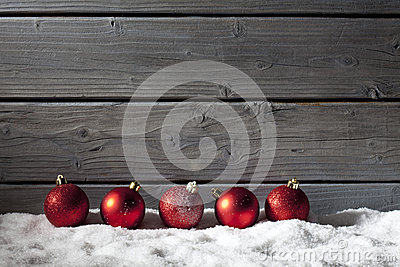 Red christmas spheres on pile of snow against wooden wall