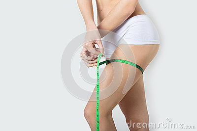 Young beautiful athletic girl measures thighs and legs measuring tape, healthy lifestyle, fitness, exercise, healthy slim body