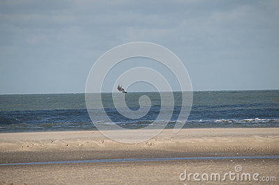 Flying kite surfer at deserted beach