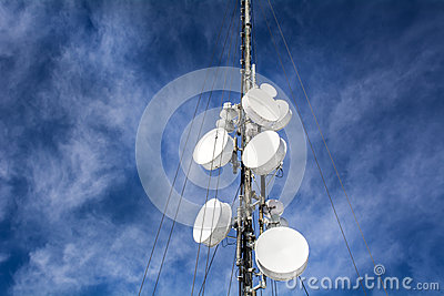 Antennas on mobile network tower on a blue sky . Global system for mobile communications.