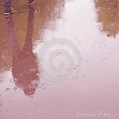 Walking people, reflection in the wet asphalt - vintage effect.