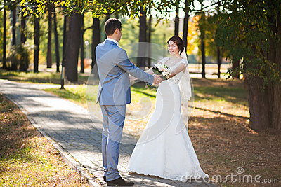 Happy bride, groom dancing in green park, kissing, smiling, laughing. lovers in wedding day. happy young couple in love.