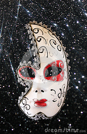 Dramatic and mysterious half moon carnival mask and black glitter background