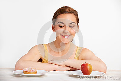 Young Woman Choosing Between Doughnut And Cake For Snack