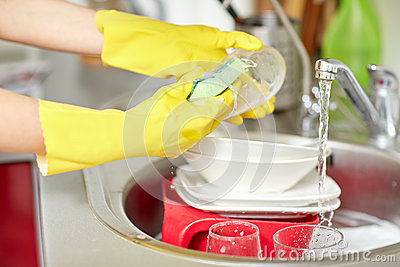Close up of woman hands washing dishes in kitchen