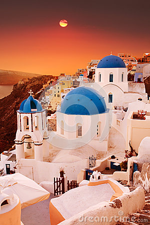 Santorini blue dome churches at sunset. Oia Village, Greece.