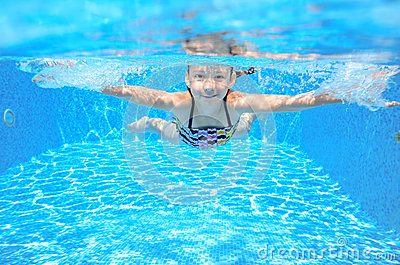 Happy girl swims in pool underwater, active kid swimming and having fun