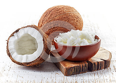 Bowl of coconut oil and fresh coconuts