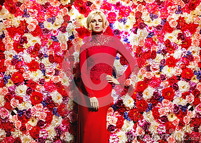 Blond slim woman over the flower wall