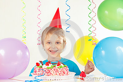 Little boy in festive hat with birthday cake and balloons