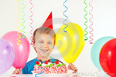 Little boy in holiday hat with birthday cake and balloons
