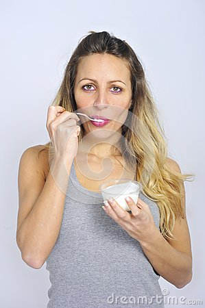 Young and attractive blond girl with spoon eating natural cream yogurt in diet healthy nutrition
