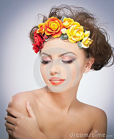 Portrait of beautiful girl in studio with red and yellow roses in her hair and naked shoulders. Sexy young woman with makeup