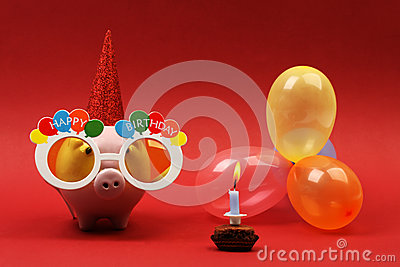 Piggy bank with sunglasses Happy birthday, party hat and multicolored party balloons on red background