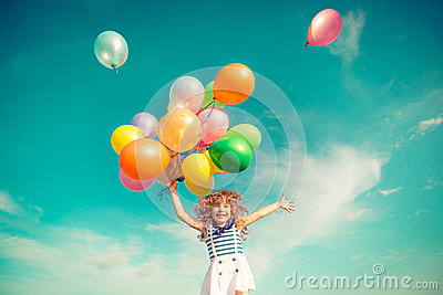 Child jumping with toy balloons in spring field