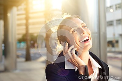 Happy business woman laughing on mobile phone outside