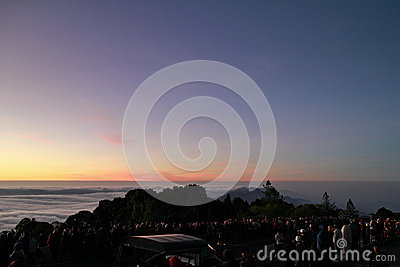 People waiting to see sun rise on top of a mountain