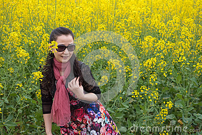 Woman and oilseed rape flowers