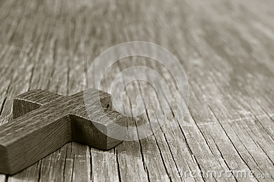 Wooden Christian cross on a rustic wooden surface, sepia toning
