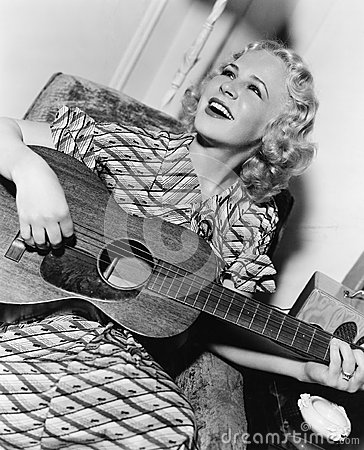 stock image of woman playing guitar and singing