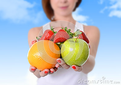 Woman showing apple, orange fruit and strawberries in hands in diet healthy nutrition concept