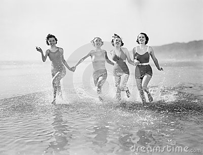 stock image of four women running in water on the beach