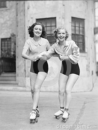 Two young women with roller blades skating on the road and smiling