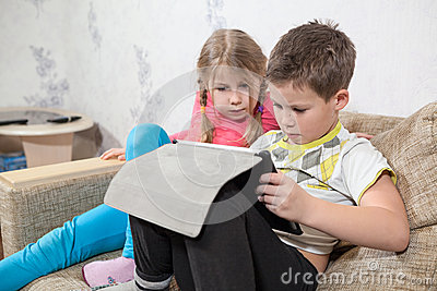 Preschool Caucasian kids having fun with pad while sitting on sofa in domestic room