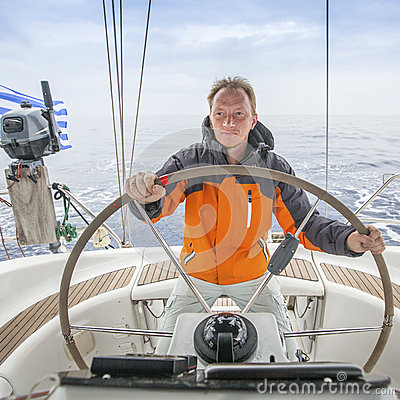 Young man Skipper early in the morning at the helm of a yacht in the open sea. Sport.