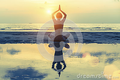 Young girl (with reflection in the water) practicing yoga on the beach during sunset.