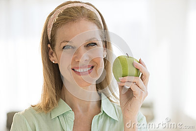 Happy Woman Holding Granny Smith Apple At Home
