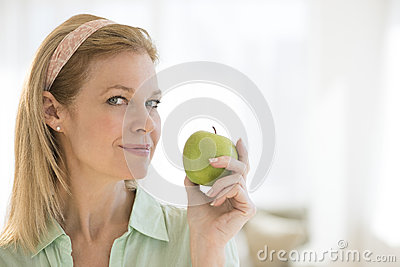 Mature Woman Holding Granny Smith Apple At Home