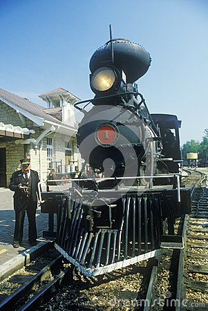 A steam engine conductor as he stands near the cowcatcher on the front, Eureka Springs, Arkansas