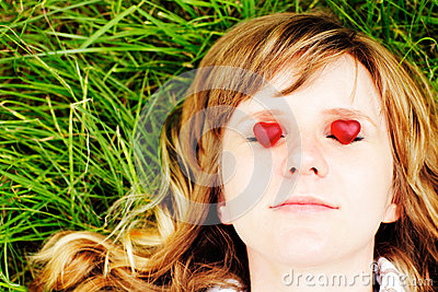 Young caucasian woman with red hair lying down on green grass with eyes closed. There are two small red sweet heart-shaped candies