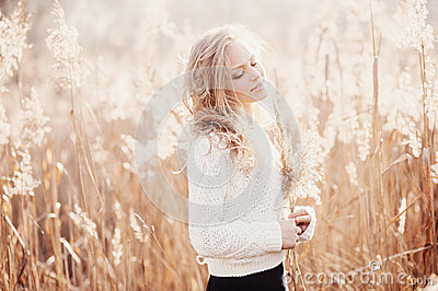 Portrait of a beautiful young blonde girl in a field in white pullover, smiling with eyes closed, concept beauty and health