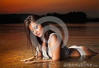 Sexy brunette woman in lingerie laying in river water. Young female relaxing on the beach during sunset. Perfect body girl