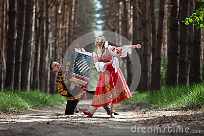 Couple dancing in russian traditional dress on nature