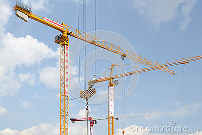 Urban industrial landscape with three tower cranes