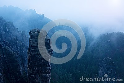 Autumn early morning view over sandstone rocks to fall valley of Saxony Switzerland. Sandstone empire and hills in mist.