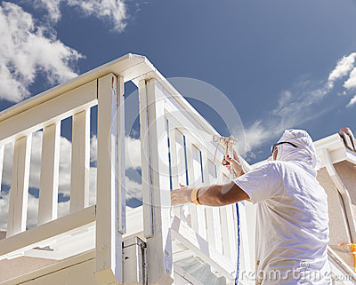 Professional Painter Spray Painting A Deck of A Home