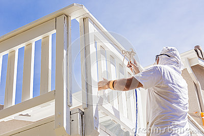 Professional House Painter Spray Painting A Deck of A Home