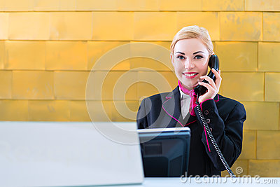 Receptionist with phone on front desk in Hotel