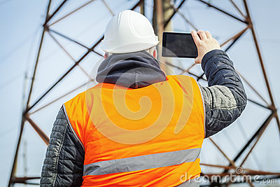 Electrical engineer filmed with tablet PC high voltage tower