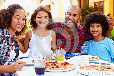 Portrait Of Family Eating Meal At Outdoor Restaurant
