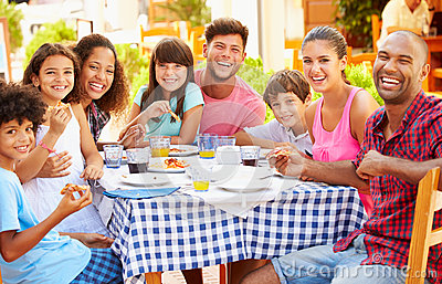 stock image of two families eating meal at outdoor restaurant together