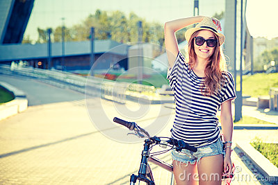 Happy Hipster Girl with Bike in the City