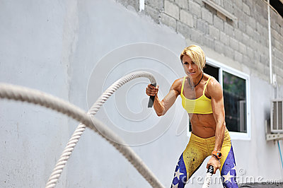 Athletic young woman doing some crossfit exercises with a rope o