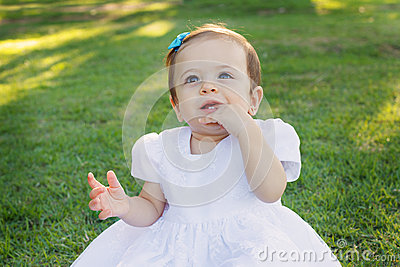 Cute happy smiling little baby girl in white dress scratching first teeth